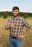 Giovane agricoltore al suo campo di grano, pollice su Fotografie Stock