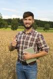 Giovane agricoltore al suo campo di grano, pollice su Immagini Stock