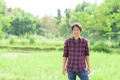 Giovane agricoltore asiatico che sta nel campo verde Fotografia Stock
