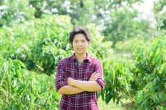 Giovane agricoltore asiatico che sta nel giardino del longan Fotografia Stock Libera da Diritti