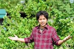 Giovane agricoltore asiatico che sta nel giardino della calce Fotografia Stock