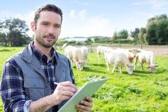 Giovane agricoltore attraente che lavora in un campo Immagini Stock