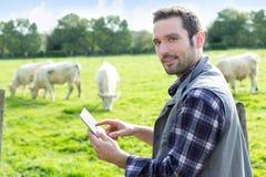 Giovane agricoltore attraente che utilizza compressa in un campo Immagine Stock