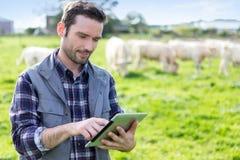 Giovane agricoltore attraente che utilizza compressa in un campo Fotografia Stock Libera da Diritti