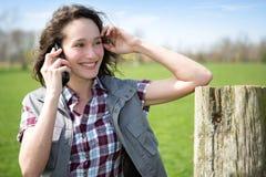 Giovane agricoltore attraente in un campo facendo uso del telefono cellulare Fotografia Stock Libera da Diritti
