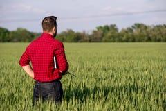 Giovane agricoltore bello con il diario che sta nel giacimento di grano Fotografie Stock