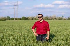 Giovane agricoltore bello con il diario che sta nel giacimento di grano Fotografia Stock