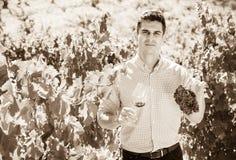 Giovane agricoltore che posa con il vino e l'uva Fotografia Stock