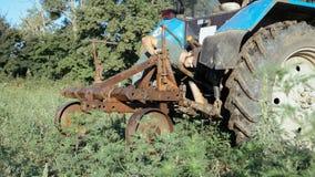 Giovane agricoltore che prepara trattore per la raccolta della patata al campo dell'azienda agricola organica Fotografia Stock