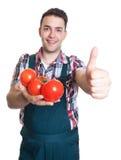 Giovane agricoltore che raccomanda i pomodori freschi Fotografia Stock Libera da Diritti