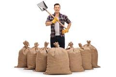 Giovane agricoltore che sta dietro i sacchi della tela da imballaggio e che tiene una pala Immagine Stock Libera da Diritti