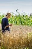 Giovane agricoltore che sta in un giacimento di grano Immagine Stock
