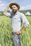 Giovane agricoltore con il cappello che sta nel grano Fotografia Stock