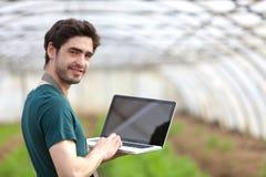 Giovane agricoltore di affari che lavora al suo computer portatile Fotografia Stock