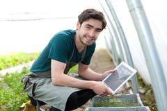 Giovane agricoltore di affari che lavora alla sua compressa Fotografia Stock Libera da Diritti
