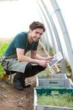 Giovane agricoltore di affari che lavora alla sua compressa Fotografie Stock