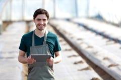 Giovane agricoltore di affari che lavora alla sua compressa Fotografia Stock