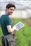 Giovane agricoltore di affari che lavora alla sua compressa Immagini Stock
