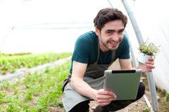 Giovane agricoltore di affari che lavora alla sua compressa Immagine Stock