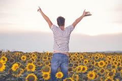 Giovane agricoltore felice che sta nel giacimento del girasole Immagini Stock