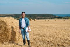 Giovane agricoltore in jeans, maglietta bianca, camicia blu, stivali di gomma nel campo con i mucchi di fieno con la compressa e  immagini stock