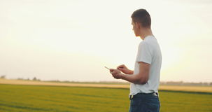 Giovane agricoltore moderno che per mezzo della compressa digitale sul campo agricolo stock footage
