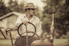 Giovane agricoltore su un trattore d'annata Immagine Stock