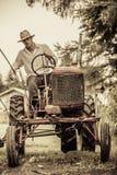 Giovane agricoltore su un trattore d'annata Fotografia Stock Libera da Diritti