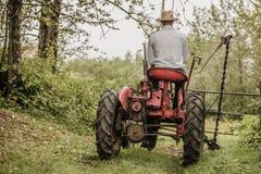 Giovane agricoltore su un trattore d'annata Fotografia Stock