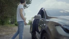 Giovane aiuto bello del tipo la sua amica da uscire dall'automobile video d archivio