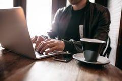 Giovane al caffè che lavora al computer portatile Fotografia Stock Libera da Diritti