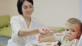 Giovane alimentazione della madre un piccolo figlio con yogurt stock footage