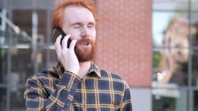 Giovane all'aperto della barba della testarossa che parla sul telefono archivi video