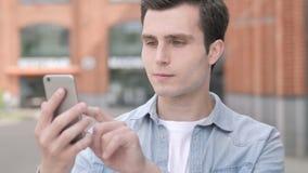 Giovane all'aperto facendo uso dello smartphone video d archivio