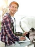 Giovane alla moda che lavora al computer portatile e che esamina macchina fotografica Immagini Stock Libere da Diritti