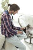 Giovane alla moda che lavora al computer portatile e che esamina macchina fotografica Fotografie Stock Libere da Diritti