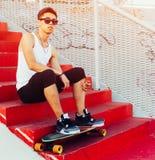 Giovane alla moda che si siede sulle scale rosse Tirante freddo Camicia bianca d'uso e pantaloni neri riposando sulle vacanze est Fotografia Stock Libera da Diritti