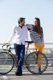 Giovane alla moda e donna che posano con la bicicletta all'aperto Immagine Stock