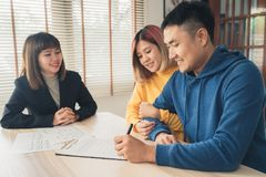 Giovane allegro che firma alcuni documenti mentre sedendosi allo scrittorio insieme alla sua moglie fotografia stock libera da diritti