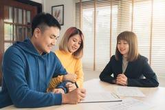 Giovane allegro che firma alcuni documenti mentre sedendosi allo scrittorio insieme alla sua moglie fotografie stock libere da diritti