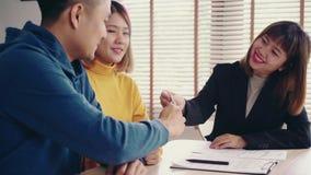 Giovane allegro che firma alcuni documenti mentre sedendosi allo scrittorio insieme alla sua moglie casa nuova d'acquisto bene im stock footage