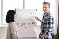 Giovane allegro che indica alla mappa di mondo Immagine Stock Libera da Diritti