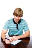 Giovane allegro che si siede ad uno scrittorio con una penna a disposizione. Immagini Stock Libere da Diritti