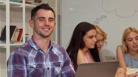 Giovane allegro che sorride allegro mentre lavorando al suo computer portatile immagini stock libere da diritti