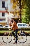 Giovane allegro con la barba che parla sul telefono cellulare e che sorride mentre vicino alla sua bicicletta immagini stock