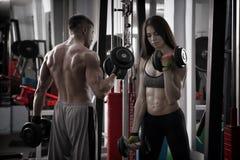 Giovane allenamento atletico sexy della donna e dell'uomo con le teste di legno in palestra Fotografia Stock Libera da Diritti