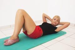 Giovane allenamento biondo della donna in ginnastica Fotografia Stock