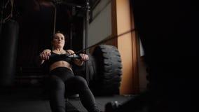 Giovane allenamento dell'atleta femminile con il simulatore di potere al rallentatore nella palestra video d archivio