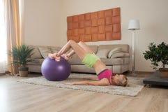 Giovane allenamento della femmina a casa Fotografia Stock