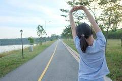 Giovane allenamento femminile prima del corso di formazione di forma fisica al parco Sta allungando il suo braccio fotografia stock libera da diritti
